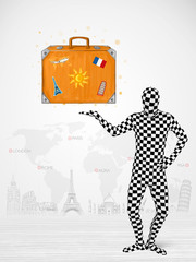 man in full body suit presenting vacation suitcase