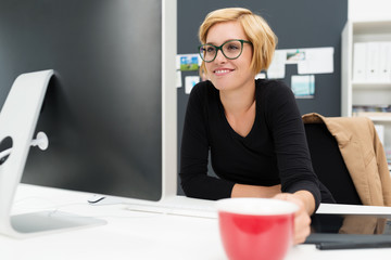 lächelnde junge frau schaut auf computer