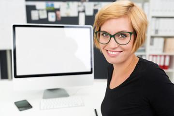 lächelnde frau mit monitor im hintergrund