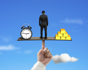 standing person between clock and gold balancing on finger seesa