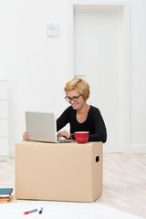 frau arbeitet am laptop in einem leeren büro