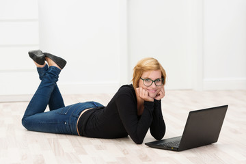 frau liegt auf dem fußboden mit ihrem notebook