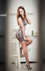 Fashionable attractive young woman in tight short dress on stool