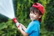 boy in cap pours water outdoor