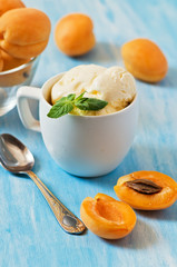 Ice cream with apricot on the blue background