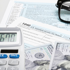USA Tax Form 1040 with glasses, calculator and 100 US dollar bil