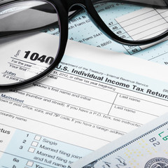 USA Tax Form 1040 with glasses and 100 US dollar bills
