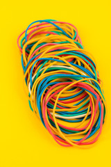 Colorful rubber bands on yellow background