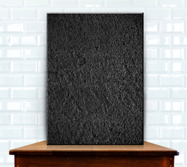 blank stone frame on wood table at white ceramic tiles wall