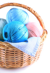Colorful yarn balls for knitting in wicker basket, isolated