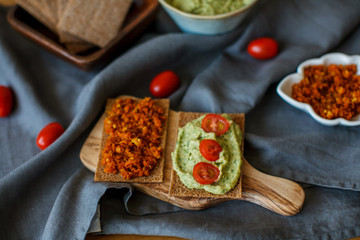 Guacamole with bread and avocado on rustic wooden background
