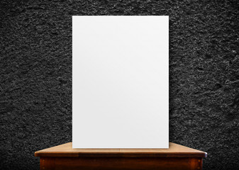 blank poster frame on wood table at black stone wall,perspective
