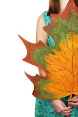 Girl holding decorative maple leaf isolated on white
