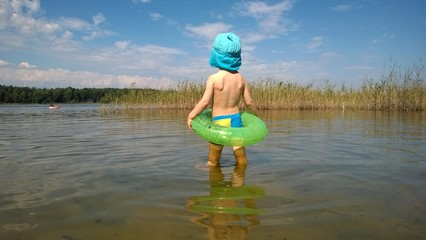 Kleiner Junge schaut verträumt über den See