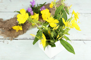 Beautiful yellow wild flowers in vase on color wooden