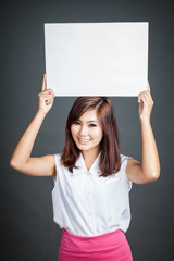 Asian girl hold blank sign over her head and smile