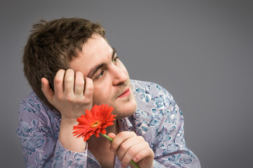 Portrait of man holding red flower