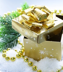 golden gift box  in the snow, christmas still life