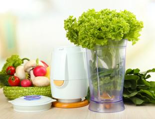 Blender with fresh vegetables on kitchen table