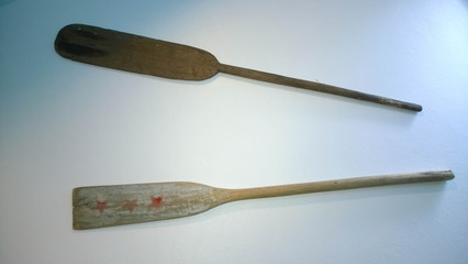 blades of old wooden weathered paddles (oars) with stains and cr