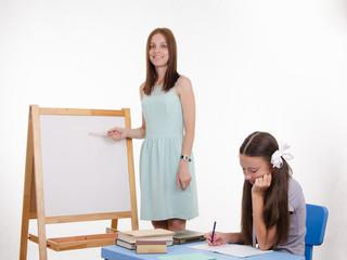 The teacher explains task at blackboard