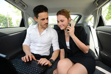 young business couple working computer in back seat  of taxi cab