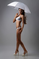 lady in lingerie with umbrella on a gray background