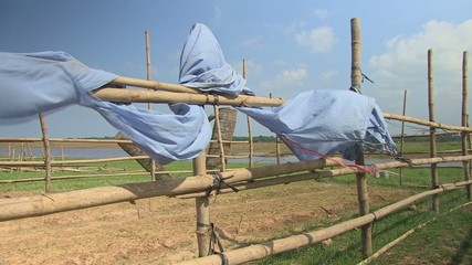 Bamboo fence with clothes suspended. The wind blows strongly