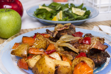 baked meat with potatoes, and watercress salad.