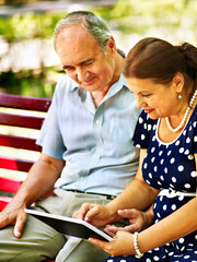 Old couple with tablet pc sit on bench .