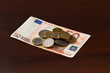Money euro coins and bills close up isolated on wooden