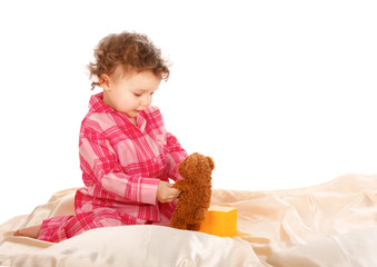 Little Girl sitting on the bed and playing isolated  white