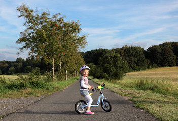 Happy little girl on her training bike outdoors
