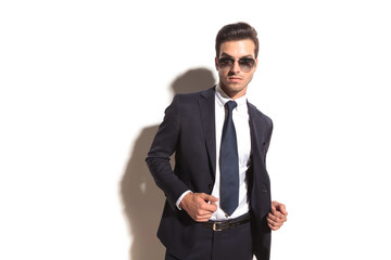sexy young business man with sunglasses opening his coat