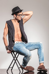 sexy young man sitting on chair relaxed