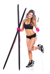 Smiling athletic woman with skis and ski poles in their hands