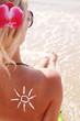 of sun cream on the female back on the beach