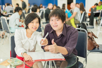 Thai (Asian) business copule are showing success gesture in the