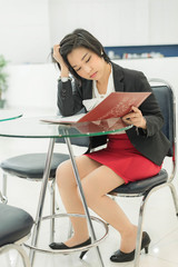 Stress Thai (Asian) businesswoman is reading her document file i