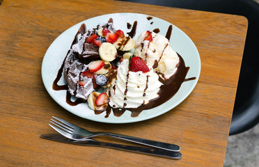 Ice cream, banana, strawberry, blueberry, chocolate waffles with