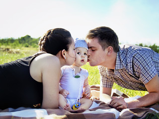 Young parents with baby outdoor in the park