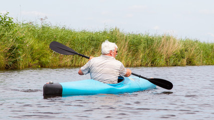 Man paddling in a blue kayak