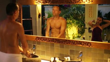 Man washing hands, woman brushing hair in luxury bathroom