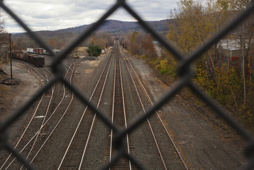 A view of a railroad track through a fence.