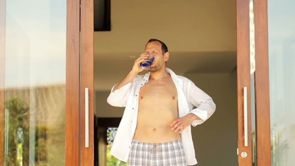 Young man drinking water, enjoying morning by luxury villa