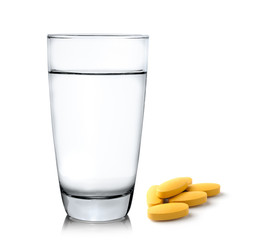 Glass of water and pills isolated on white background