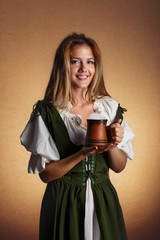 woman in tiroler oktoberfest dress with big mug of beer in hands