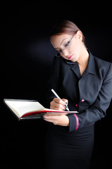 Woman Taking Notes While Talking on Phone