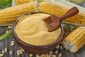 corn grits polenta in a wooden bowl on old wooden table