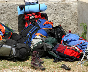 backpacks bags and boots piled up after the long walk of the boy